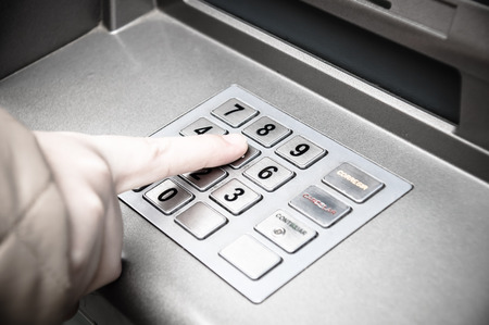 pin code: woman hand entering pin code in a ATM