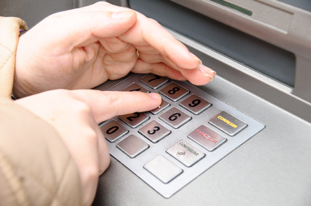 cashpoint: woman hand entering pin code in a ATM