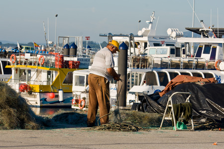 O GROVE, SPAIN - SEPTEMBER 14: Fisherman repairing fishing net on September 14, 2012 in O Grove, Galicia, Spain. The Rias Baixas are a series of four estuarine inlets located on the southwestern coast of Galicia, Spain.