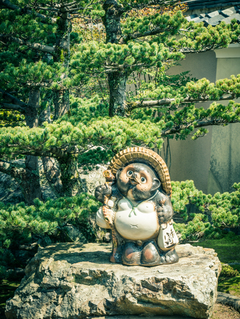 statuary: ARASHIYAMA, JAPAN - MARCH 29: Traditional japanese Tanuki  on March 29, 2015 in Arashiyama, Japan. It is a common theme in Japanese art, especially statuary.