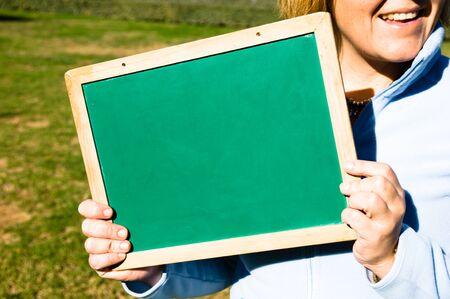 green chalkboard: woman holding a green chalkboard