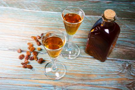 cognac: Close-up of glasses of cognac, bottle and raisin Stock Photo