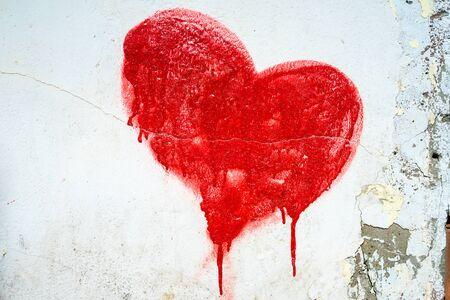 Rot bemalte Herz auf blauer gebrochener Wand