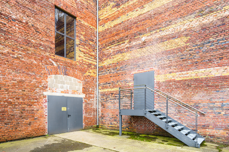 metal gate: View on urban brick building with metal gate and stairway Stock Photo