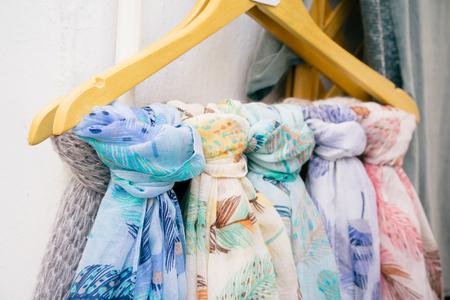 scarves: Bright ornamental scarves hanging on metal bar for sale outdoor