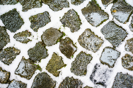 cobbled: Close-up of cobbled floor with snow and green grass