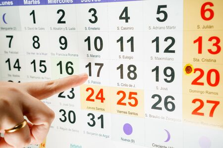 incognito: Unrecognizble person pointing at special day of week Stock Photo