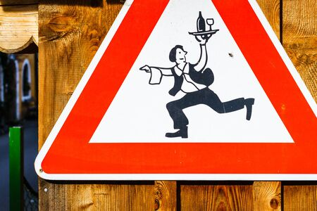 hurrying: Close-up of roadsign with hurrying waiter holding tray with drink on wooden background