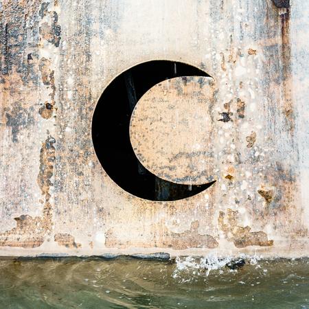 half moon: View on rusty wall with half moon near water. Water drops falling. Stock Photo