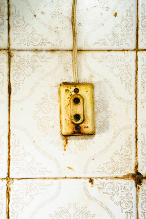 untidy: Close-up of untidy rustic socket on ceramic wall