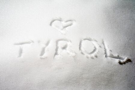 written: Tyrol written on snow surface Stock Photo