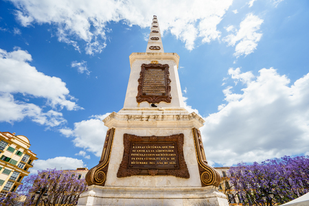 merced: MALAGA,SPAIN - 28 MAY 2016:View on famous monument on Merced square against of blue sky with white clouds.From below