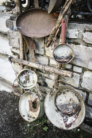 decayed: Decayed iron kitchenware outdoor against of stone wall