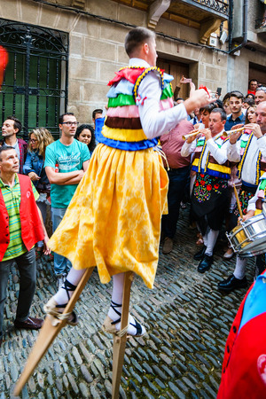 LA RIOJA,SPAIN - 29 AUGUST,2016:Crowd of people watching four men in bright festiva costumes in the street.Anguiano festival Editorial