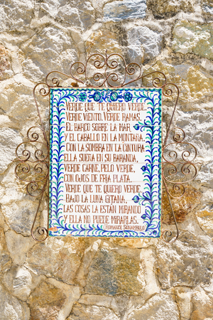 garcia: ALFACAR,GRANADA,SPAIN - 31 AUGUST,2016:Close-up of ornamental signboards with frame on stone wall in Garcia Lorca Park Editorial