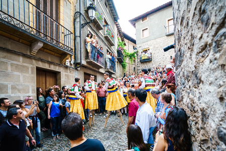 festiva: LA RIOJA,SPAIN - 29 AUGUST,2016:Crowd of people watching four men in bright festiva costumes in the street.Anguiano festival Editorial