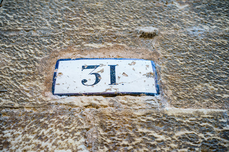 wornout: Close-up of worn-out metal signboard with house number Stock Photo
