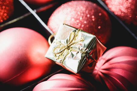 plaything: Close up of red festive baubles and tiny gold gift box in package Stock Photo