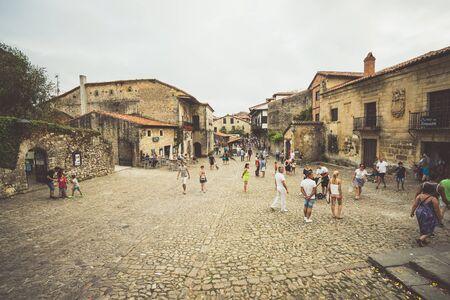 empedrado: Santillana del Mar, Cantabria, ESPAÑA - 31 de agosto 2016: Multitud de personas caminando en la plaza pavimentada de la ciudad vieja