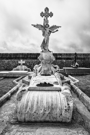 COMILLAS,CANTABRIA,SPAIN - 31 AUGUST,2016:Black and white statue on tomb with catholic cross against of overcast sky