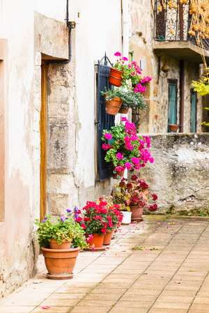 Ezcaray, La Rioja, Spain - 11.13.2016: Old stone street with flowers in pots.