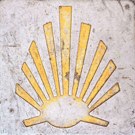 Way of St. James  - 11.09.2016 From above shot of yellow scallop shell symbol on concrete. Редакционное