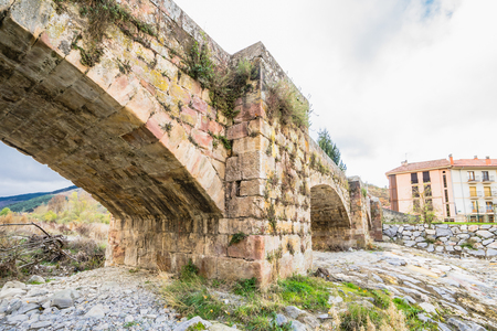 Ezcaray, La Rioja, Spain - 13.11.2016: Old stone bridge at Oja River. The town is situated at the base of the San Lorenzo peak and is 13 km from the Valdezcaray ski area.