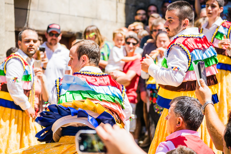 empedrado: LA RIOJA,SPAIN - 23 JULY,2017:Crowd of people watching four men in bright festival costumes in the street.Anguiano festival Editorial