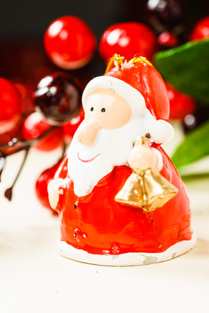 Close up of Christmas decorations and figurine of Santa Claus with bells standing on wooden surface.