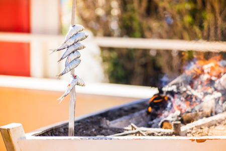 skewer with sardines (espetos) in a fire. Typical spanish cuisine. Stock Photo