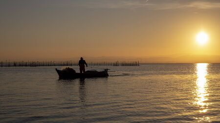 Man fishing in a boat at sunset in Albufera of Valencia, Valencia, Spain.