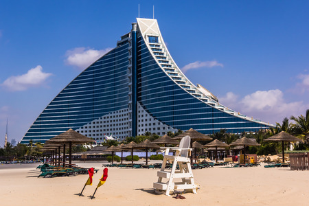 preceded: Dubai, UAE - February 3, 2015: Jumeirah Beach Hotel, preceded by the beachfront. Well-known for its wave-shaped silhouette, remains one of the best recognizable landmarks of Dubai. Editorial