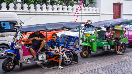 drivers: Bangkok, Thailand - October 31, 2014: Motor bike rickshaw drivers wait for clients at the entrance to the Temple of the Reclining Buddha. Motor bike rickshaws replaced traditional bike based model.