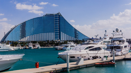 preceded: Dubai, UAE - February 3, 2015: Jumeirah Beach Hotel, preceded by the luxury marina. Wave-shaped resort, next to famous Burj Al Arab, remains one of the well-known landmarks  of Dubai.