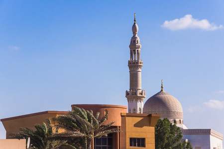 preceded: Dubai, UAE - February 3, 2013: The  Maharba mosque in Dubai, located in Jumeirah district, along the beach, preceded by the residential building. Editorial
