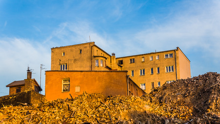 remained: Debris remained after demolishing an old tenement with sun-flooded residential buildings in the background, in Katowice, Silesia region, Poland.