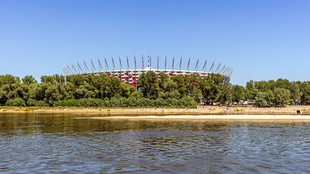 preceded: Warsaw, Poland - July 3, 2015: The Polish National Stadium preceded by the municipal beach on Vistula river. Designed and constructed for UEFA EURO 2012 tournament co-hosted by Poland and Ukraine. Editorial