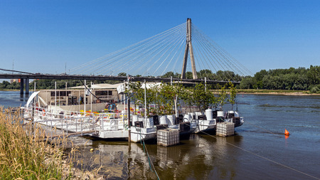 preceded: Warsaw, Poland - July 3, 2015: The Swietokrzyski Bridge over Vistula river preceded by the floating restaurant, first modern cable-stayed bridge in Warsaw, 479 m long with the tower 90 m high. Editorial