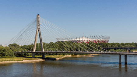 preceded: Warsaw, Poland - July 3, 2015: The National Stadium preceded by The Swietokrzyski bridge over Vistula river. Designed and constructed for UEFA EURO 2012 tournament co-hosted by Poland and Ukraine.