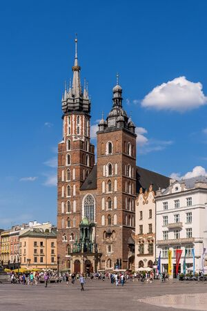 crown spire: Krakow, Poland - June 3, 2015: Old Market Square crowded with tourists at the St. Marys Basilica. Brick Gothic church built in the early 13th century is the main landmark of the city. Editorial