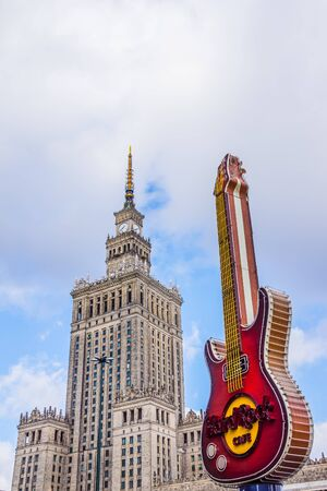 preceded: Warsaw, Poland - Mar 01, 2013: Palace of Culture and Science, built in a socialist realism style city landmark, preceded by the guitar, famous symbol of Hard Rock Caf situated nearby. Editorial