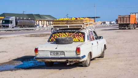 Zarat, Azerbaijan - September 13, 2013: Old type car fully loaded with apples by the highway. Individual economic activity is still very important in rapidly developing Azerbaijan. Editorial