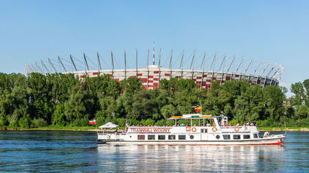 preceded: Warsaw, Poland - May 19, 2013: The Polish National Stadium preceded by the pleasure boat on the Vistula river.  Designed and built for UEFA EURO 2012 tournament co-hosted by Poland and Ukraine. Editorial