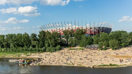 preceded: Warsaw, Poland - May 19, 2013: The Polish National Stadium preceded by the beach on Vistula river bank.  Designed and constructed for UEFA EURO 2012 tournament co-hosted by Poland and Ukraine.