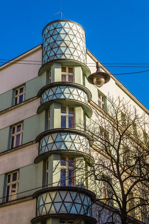 tenement: Tenement being an interesting example of modernism architectural style in Gliwice on February 08, 2014. Characteristic rounded corner is filled with milk glass, which is illuminated at night. Editorial