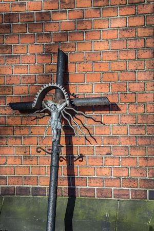 Abgenutztes Grabstein Jesus-Kreuz, das an der chapell Wand auf dem Kirchhof in Katowice, Schlesien-Region, Polen sich lehnt. Standard-Bild - 42648274