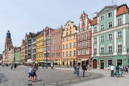 town halls: Wroclaw, Poland - May 16, 2015: Tourists and locals walk in the area of the 13th century Main Market Square, one of the largest markets in Europe, with the largest two town halls in Poland.