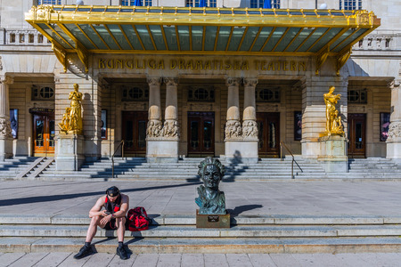 passerby: STOCKHOLM - AUGUST 10, 2015: Unidentified passerby sits by the August Strindberg bust in front of the Royal Dramatic Theater. The theatre is located in the Art Nouveau building at Nybroplan since 1908