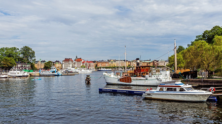 prestigious: STOCKHOLM - AUGUST 10, 2015: Boats moored at the Skeppsholmen islet and view on Strandvagen, a boulevard completed for the Stockholm Worlds Fair in 1897, the most prestigious avenue in town.