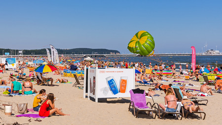 baltic people: SOPOT, POLAND - AUGUST 15, 2015: People sunbath on the beach in Sopot, major SPA and tourist resort on the Polish Baltic Sea coast. In the background the longest wooden pier in Europe at 511 m.